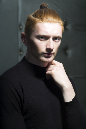 young unshaven: Portrait of handsome stylish young unshaven guy with red hair with ponytail standing in black jersey with hand near neck looking forward indoor on studio , vertical picture
