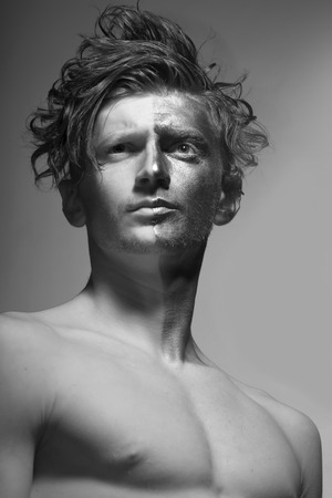 bronzy: One young fashionable painted man model with silver bodyart on one half of face and stylish hairdo with bare chest looking away standing on studio black and white, vertical picture Stock Photo