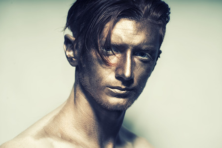 bronzy: Portrait of young fashionable painted man model with bronze bodyart on face and stylish hairdo looking forward standing in studio on white , horizontal picture Stock Photo