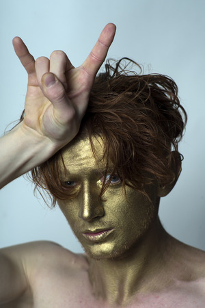 bronzy: Portrait of young fashionable painted man model with golden bodyart on face and stylish red hairdo holding hand in cool gesture looking forward standing in studio on blue , vertical picture Stock Photo