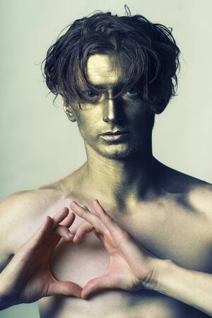 bare chest: One young fashionable painted man model with golden bodyart on face and stylish hairdo holding hands in shape of heart on bare chest standing in studio on white , vertical picture