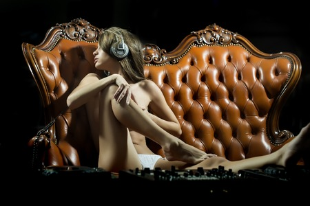 Sexy young naked dj woman in white panties and headphones with bare chest and nipples sitting at table with mixer console on brown leather royal sofa in night club, horizontal picture Banque d'images