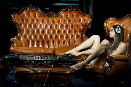 Sensual sexy undressed dj girl in headphones with bare chest sitting on chair at table with mixer console and brown leather royal sofa in night club copyspace, horizontal picture