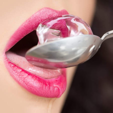 Closeup of pretty open female mouth of beautiful young woman with bright pink lips licking cold fresh crystal ice cube on silver colour spoon with tongue, square picture