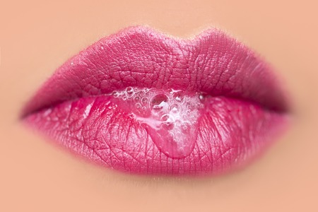 sexual health: Closeup of sexual closed female mouth of beautiful young woman with foam beverage bubbles on bright pink lips on tan beige face, horizontal picture