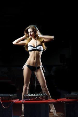 ropa interior femenina: Hermosa joven rubia chica dj sexy en ropa interior y los auriculares con el pelo largo y el baile cuerpo recto en la mesa de color rojo con la consola mezcladora en club nocturno sobre un fondo oscuro, imagen vertical Foto de archivo