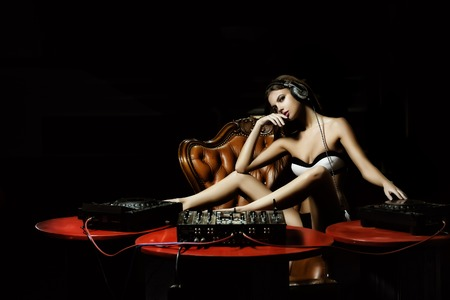 Attractive young glamour dj woman in lingerie and headphones sitting at red table with mixer console on brown leather royal chair in night club on dark background, horizontal picture