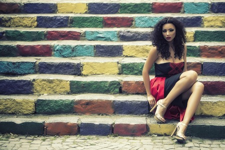 sitting pretty: Beautiful sexual young brunette girl with curly hair in black and red dress on high heels sitting on colorful stairs blue orange yellowe violet and green colors outdoor copyspace, horizontal picture
