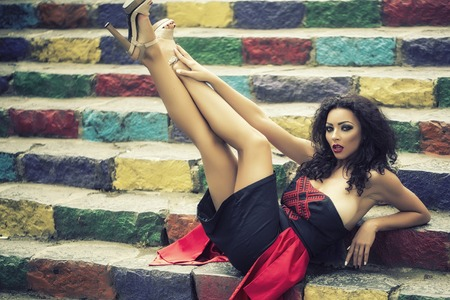busty: Pretty sexual young brunette busty girl with curly hair in black and red dress lying on colorful stairs blue orange yellowe violet and green colors outdoor with raised legs, horizontal picture
