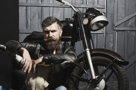 Thoughtful unshaven male biker in leather jacket sitting near motorcycle in garage with big bone skull antlers of stuffed animal looking forward on wooden wall , horizontal picture