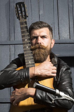 fingerboard: One serious unshaven musical man with beard and handlebar moustache holding acoustic string guitar with finger-board looking forward indoor on wooden wall black and white, vertical picture
