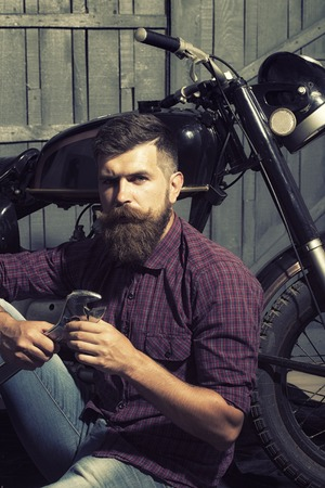 alligator wrench: Young unshaven male biker in purple checkered shirt and jeans sitting near motorcycle in garage holding metallized iron spanner looking forward on workshop , vertical picture