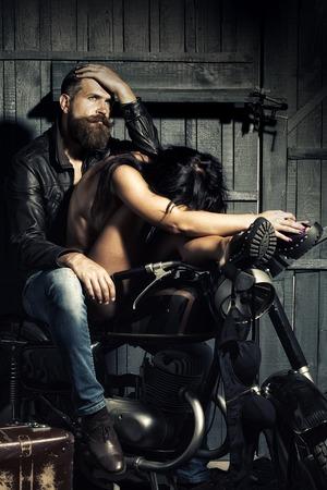 femme se deshabille: Jeune couple sexy de motard pensive mal rasé en veste de cuir et jeans avec déshabillée femme brune assis ensemble sur la moto dans le garage sur le mur en bois, image verticale