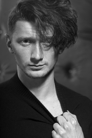 young unshaven: Portrait of handsome young unshaven male with stylish hairdo standing in jersey with hand near neck looking forward indoor on studio black and white, vertical picture