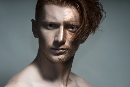 bronzy: Portrait of young fashionable painted red man model with bronze bodyart on one half of face and stylish hairdo looking forward standing in studio on grey , horizontal picture Stock Photo