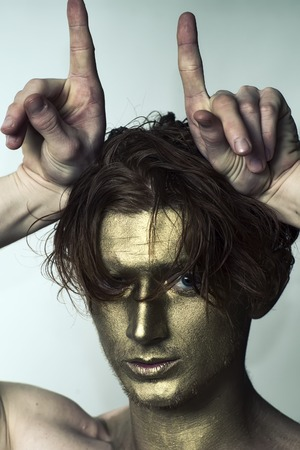 bronzy: Portrait of young fashionable painted man model with golden bodyart on face and stylish hairdo holding hands as antlers looking forward standing in studio on white , vertical picture