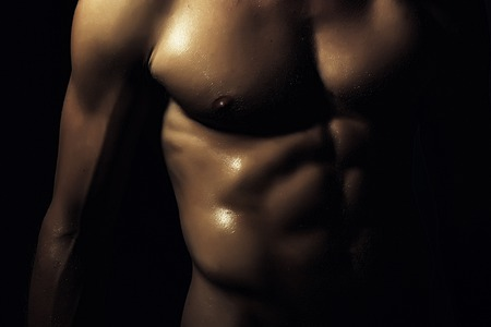 boy  naked: Closeup of young naked man with sexual strong muscular beautiful tan wet body with sexy chest and nipples standing on black backgrouns, horizontal picture