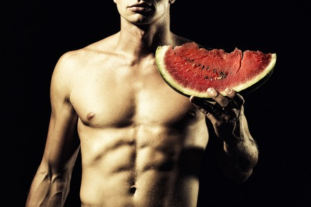 naked black men: Young sexual naked man with beautiful strong muscular body holding big juicy red water melon slice standing on black background, horizontal picture
