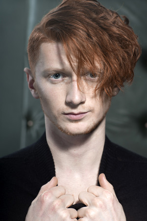 young unshaven: Portrait of attractive stylish young unshaven guy model with red hair holding collar with hands standing in black jersey looking away indoor on studio background closeup, vertical picture Stock Photo