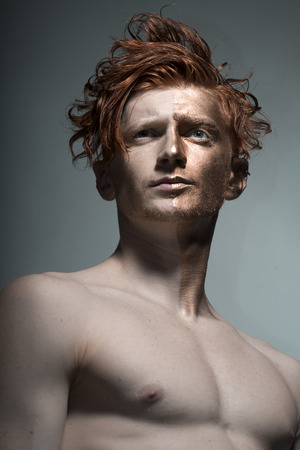 bronzy: One young fashionable painted man model with bronzy bodyart on one half of face and stylish red hairdo with bare chest looking away standing in studio on grey background, vertical picture