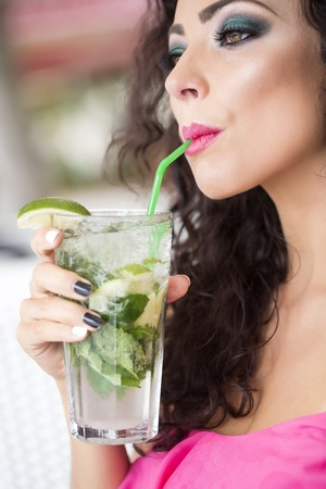 Profile of sexual cute young woman with curly hair and bright makeup drinking alcoholic mojito cocktail from mint soda light rum and lime with straw, vertical picture Stock Photo