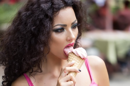 licking tongue: Portrait of sexy young brunette lady with curly hair and bright makeup licking cold dessert of red berry ice cream cone with tongue and open mouth, horizontal picture