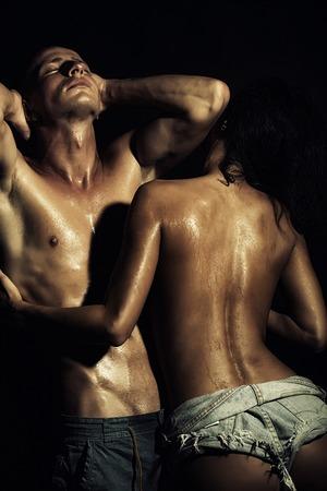 m�nner nackt: Sexy junge Paar nackter Mann mit starken muskul�sen sch�nen nassen K�rper und ziemlich schlank tan M�dchen in Jeans-Shorts umfassende stand auf schwarz Studio Hintergrund, vertikale Bild,