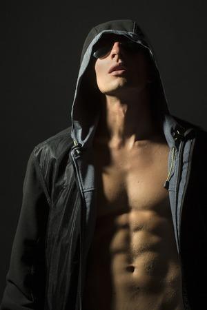 nackter junge: Junge entkleidet Kerl mit sexy starken muskulösen schönen Körper in schwarzem Leder-Jacke mit Kapuze und Sonnenbrille, die auf Studio grauen Hintergrund, vertikale Bild, Lizenzfreie Bilder