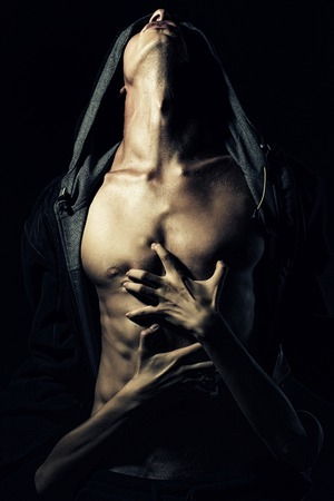 Young pair of boy with sexy strong muscular body in leather jacket with hood looking up and woman embracing with hands standing on studio black background, vertical picture