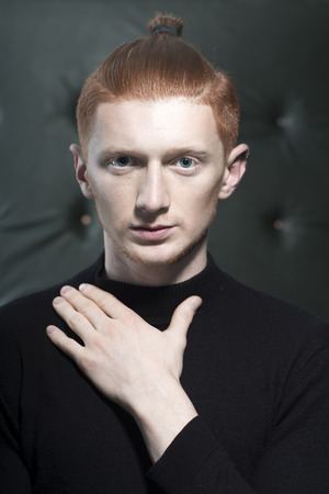 young unshaven: Portrait of handsome stylish young unshaven man with red hair with ponytail standing in black jersey with hand on chest looking forward indoor on studio background, vertical picture