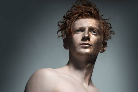 bronzy: One young fashionable painted man model with bronzy bodyart on one half of face and stylish red hairdo looking away standing in studio on grey background, horizontal picture Stock Photo