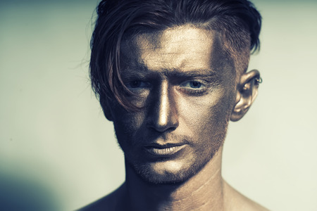 bronzy: Closeup of young fashionable painted man model with bronze bodyart on face and stylish hairdo looking forward standing in studio on white background, horizontal picture Stock Photo