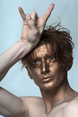 bronzy: Portrait of young fashionable painted man model with bronzed bodyart on face and stylish hairdo holding hands in cool gesture looking away standing in studio on blue background, vertical picture