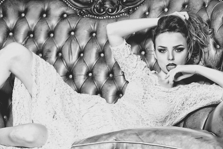 glamour nude: Attractive confident young stylish woman in lace dress with bright makeup looking forward lying on leather royal sofa indoor black and white, horizontal picture