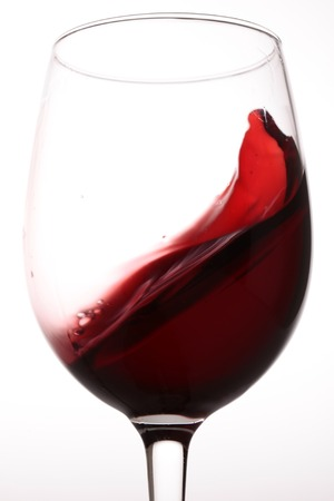 Close-up van een mooi helder glas beker met spatten lekker zoet dessert rode druiven wijn met bubbels in staande positie op een witte achtergrond studio, verticaal beeld