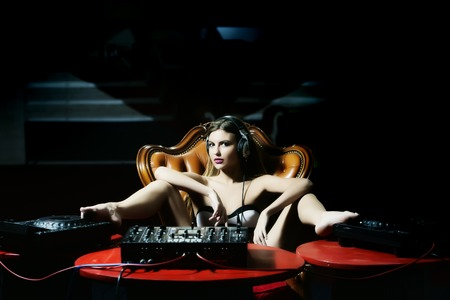 Sexual young glamour dj woman in lingerie and headphones sitting at red table with mixer console on brown leather royal chair in night club on dark background, horizontal picture Stockfoto
