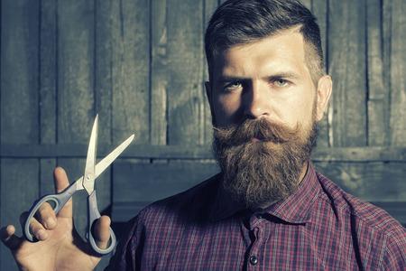 bigote: Retrato de hombre sin afeitar, con camisa a cuadros violeta con larga barba y bigote que sostiene unas tijeras afiladas ganas de pie en el fondo de pared de madera, cuadro horizontal