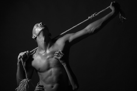 female sex: Young stripped handsome man with sexy strong muscular body with long durable rope and female hands standing on studio background black and white, horizontal picture