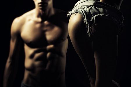männer nackt: Nahaufnahme des jungen entkleidete Paar sexy Frau in Jeans mit schönen Gesäß und ein Mann mit starken muskulösen Körper, die auf schwarzem Hintergrund Studio, horizontal Bild