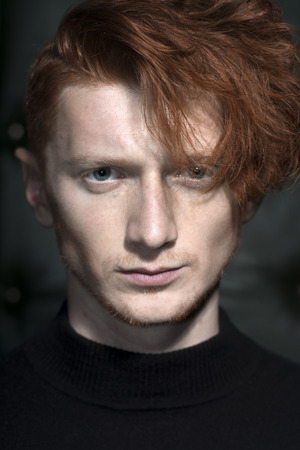 young unshaven: Portrait of handsome stylish young unshaven man model with red hair standing in black jersey looking forward indoor on studio background closeup, vertical picture Stock Photo