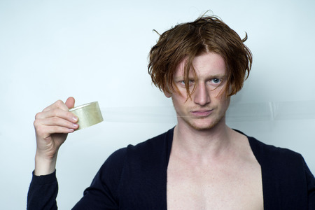 scotch tape: Portrait of sexy attractive young man model with red hair in black jersey with beautiful chest holding scotch tape looking forward standing in studio on white background copyspace, horizontal picture