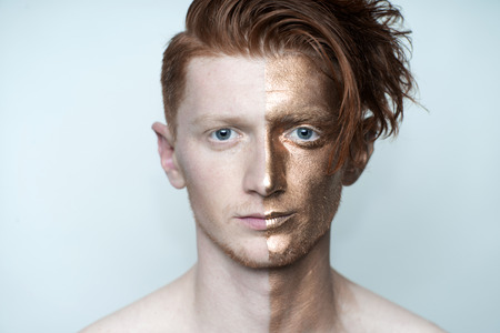 bronzy: Portrait of young fashionable painted man model with bronze bodyart on one half of face and stylish red hairdo looking forward standing in studio on white background, horizontal picture