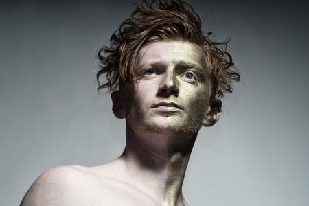 red man: Retrato del modelo de hombre pintado de moda con bodyart de Oro en una mitad de la cara y elegante peinado rojo mirando a otro lado de pie en el estudio sobre fondo blanco, cuadro horizontal
