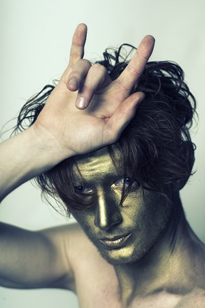 bronzy: Portrait of young fashionable painted man model with golden bodyart on face and stylish hairdo holding hands in cool gesture looking forward standing in studio on white background, vertical picture Stock Photo