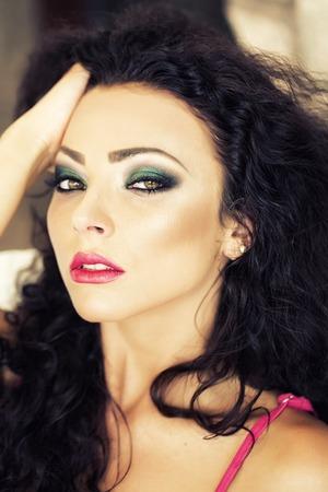 곱슬 머리 밝은 메이크업 잠겨있는 아름 다운 젊은 갈색 머리 여자의 초상화 표현 녹색 갈색 눈과 앞으로 앉아 야외, 세로 그림을 찾고 핑크 입술