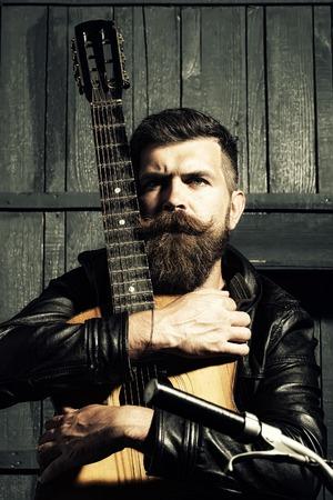 capelli lunghi: Un creativo barba lunga uomo musicale con barba e baffi a manubrio azienda chitarra acustica stringa con il dito a bordo in attesa coperta su sfondo parete in legno bianco e nero, foto verticale