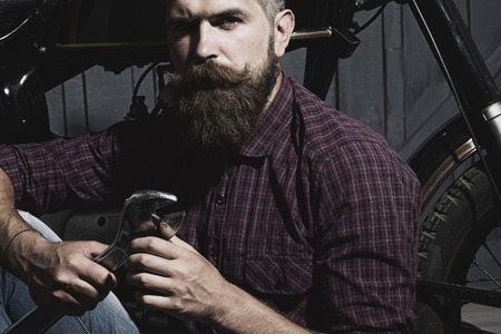 young unshaven: Young unshaven male biker in purple checkered shirt sitting near motorcycle in garage holding metallized iron wrench looking forward on workshop background, horizontal picture