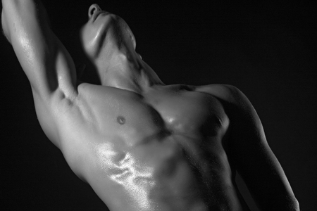 One young naked handsome man with sexy strong muscular wet body with raised hand standing on studio background black and white, horizontal picture Stock Photo