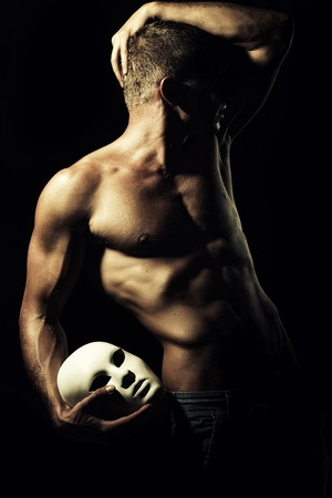 nude: One young undressed faceless man with sexual strong muscular attractive body with raised hand and beautiful chest holding one white mask standing on black studio background, vertical picture