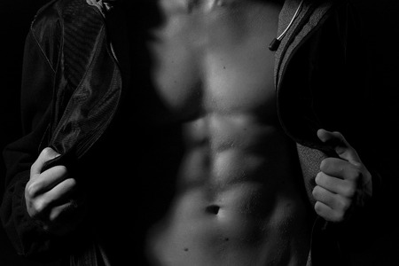 nude boy: Closeup of young undressed guy with sexy strong muscular beautiful body in leather jacket with hood standing in studio black and white, horizontal picture
